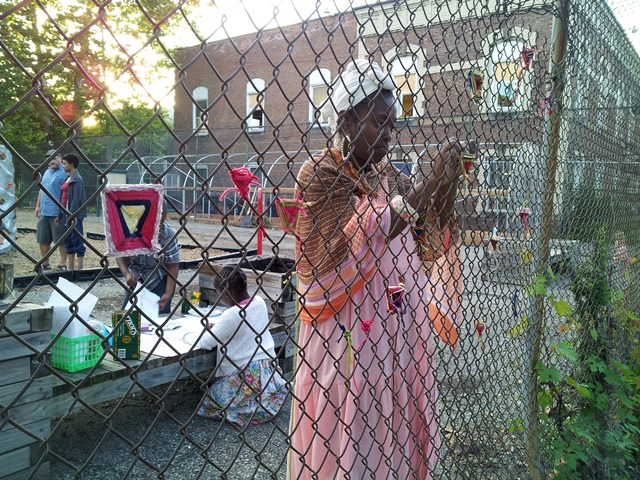 Weaving Protective Eyes, Ojo de Dios, into the Boggs School fence, August 2014, Detroit